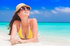Vrouw in bikini en strohoed die genietend van zonnige dag op tropisch strand liggen royalty-vrije stock afbeelding