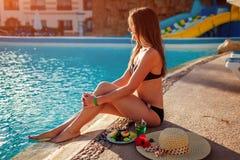 Vrouw in bikini het drinken cocktail en het eten van vruchten door zwembad Inclusief allen De vakantie van de zomer stock foto's
