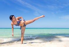 Vrouw in bikini het praktizeren schoppen Stock Afbeeldingen