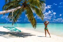 Vrouw in bikini onder palm op overzeese achtergrond stock afbeeldingen