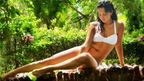 Vrouw in bikini onder tropische vegetatie Stock Afbeeldingen