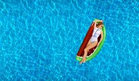Vrouw in bikini op de opblaasbare matras in het zwembad stock foto's