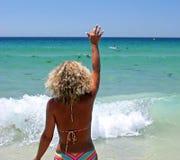 Vrouw in bikini op wit strand dat aan haar echtgenoot golft royalty-vrije stock foto's