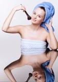 Vrouw in blauwe badhanddoek op hoofd met make-upborstel Royalty-vrije Stock Afbeelding