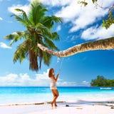 Vrouw in blauwe kleding die bij strand slingeren Stock Foto