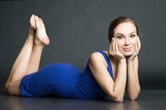 Vrouw in blauwe korte kleding die op donkere achtergrond liggen Royalty-vrije Stock Afbeeldingen