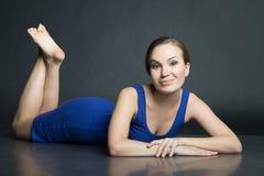 Vrouw in blauwe korte kleding die op donkere achtergrond liggen Royalty-vrije Stock Foto's