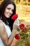 Vrouw in bloemtuin die rode rozen ruikt Stock Foto