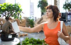 Vrouw in bloemwinkel stock afbeelding