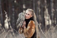 Vrouw blond in de herfst in bontjas met uil op hand eerste sneeuw B stock fotografie