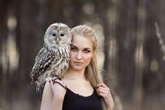Vrouw blond in de herfst in bontjas met uil op hand eerste sneeuw B royalty-vrije stock afbeelding