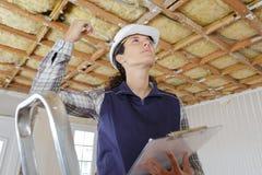 Vrouw in bouwer eenvormig op ladder binnen stock fotografie