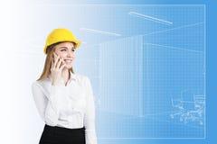 Vrouw in bouwvakker en blauwdruk Stock Foto
