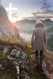 Vrouw bovenop de berg die in Christian Cross bekijken Royalty-vrije Stock Afbeeldingen