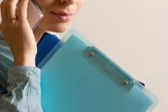 vrouw-bureau arbeider die op de telefoon met veel omslagen op hand spreken stock afbeelding