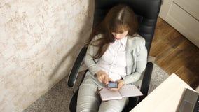 Vrouw in bureau die in werkplaats rusten de mooie onderneemster met telefoon zit als voorzitter met naakte voeten op de lijst stock videobeelden