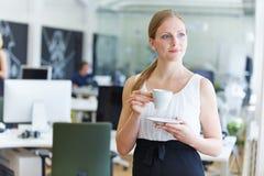 Vrouw in bureau het drinken koffie royalty-vrije stock afbeeldingen