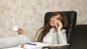Vrouw in bureau het drinken koffie die in werkplaats rusten de mooie onderneemster met telefoon zit als voorzitter met naakte voe royalty-vrije stock foto