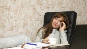 Vrouw in bureau het drinken koffie die in werkplaats rusten de mooie onderneemster met telefoon zit als voorzitter met naakte voe stock foto