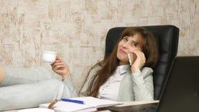 Vrouw in bureau het drinken koffie die in werkplaats rusten de mooie onderneemster met telefoon zit als voorzitter met naakte voe royalty-vrije stock afbeeldingen