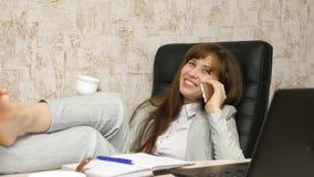 Vrouw in bureau het drinken koffie die in werkplaats rusten de mooie onderneemster met telefoon zit als voorzitter met naakte voe stock fotografie