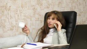 Vrouw in bureau het drinken koffie die in werkplaats rusten de mooie onderneemster met telefoon zit als voorzitter met naakte voe stock afbeeldingen