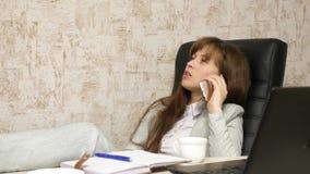 Vrouw in bureau het drinken koffie die in werkplaats rusten de mooie onderneemster met telefoon zit als voorzitter met naakte voe royalty-vrije stock afbeelding