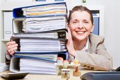 Vrouw in bureau met stapel dossiers Stock Foto's