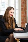 Vrouw in bureauzitting op de computer stock foto