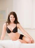 Vrouw in bustehouder en ondergoed het stellen op bed Stock Fotografie