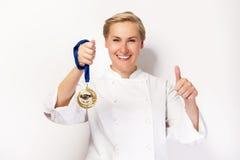 Vrouw in chef-kokuitrusting met duim omhoog en het eerste prijsmedaille glimlachen stock afbeeldingen