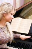 Vrouw in cocktailkleding en piano Stock Afbeelding