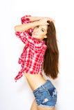 vrouw in controleoverhemd, jeansborrels op witte achtergrond Stock Foto