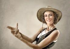 Vrouw in cowboyhoed, die gebaar met handen maken die kanon beweren stock foto