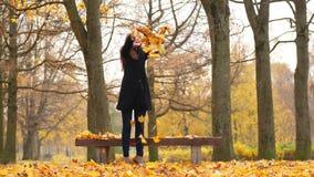 Vrouw dansen, die in bladeren van de lucht de heldere esdoorn werpen stock footage