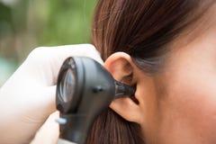 Vrouw de arts controleert het oor van de patiënt met materiaal stock foto