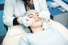 Vrouw de arts leidt een medische procedure om het gezicht van een jong meisje schoon te maken stock foto