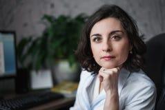 Vrouw de arts met aandachtige ernstig bekijkt in witte medische robezitting een lijst Op de lijstboeken, een computermonitor en a stock afbeeldingen