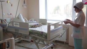 Vrouw de arts toont een elektronisch bed voor geduldige zorg aan 4K stock videobeelden