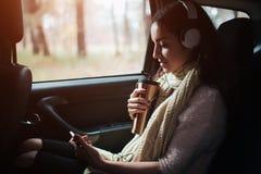 Vrouw in de auto, de herfstconcept Glimlachend mooi meisje die aan muziek met hoofdtelefoons luisteren en een boek lezen die zich royalty-vrije stock afbeelding