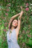 Vrouw in de bloeiende takken van een boom stock fotografie