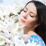 Vrouw in de bloemen van magnolia stock afbeelding