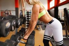 Vrouw, de blond bij de gymnastiek, neemt domoren, die aan de triceps werken stock foto