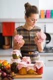 Vrouw in de domeinen van de keukenholding en het bekijken kruiken Stock Afbeeldingen