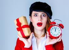 Vrouw in de doos van de Kerstmisgift van de hoedenholding en rode retro wekker stock foto