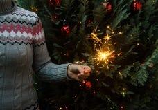 Vrouw in de gebreide sterretjes van de sweaterholding vóór Kerstmisboom royalty-vrije stock afbeeldingen
