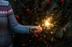 Vrouw in de gebreide sterretjes van de sweaterholding vóór Kerstmisboom royalty-vrije stock afbeelding