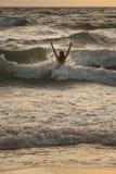 Vrouw in de golven op zonsondergang Stock Afbeelding