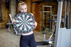 Vrouw in de gymnastiek die een dartboarddoel houden Het concept succes en voltooiing van doelstellingen, resultaten royalty-vrije stock afbeeldingen