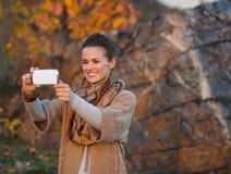 Vrouw in de herfstavond die in openlucht foto nemen Royalty-vrije Stock Fotografie